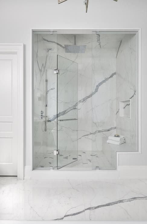 Photo of A statuary marble floor leads to a seamless glass shower boasting marble floor t…