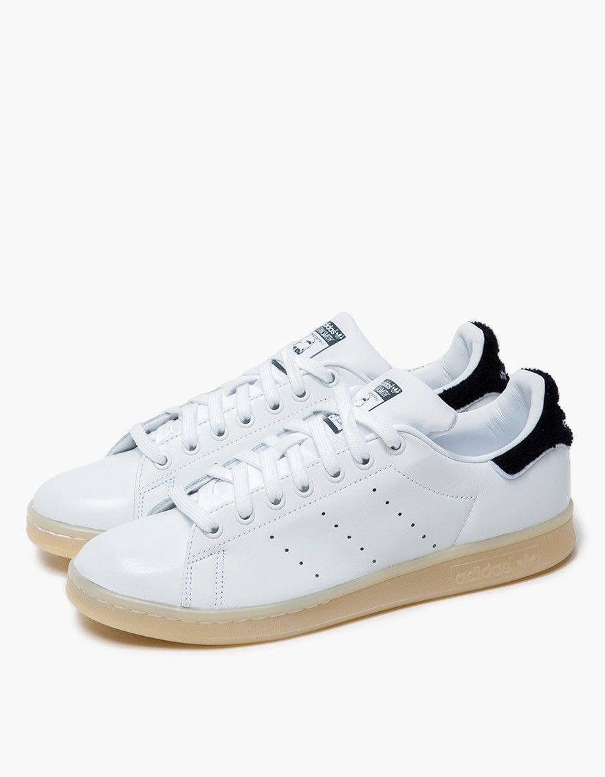 the latest 72add 07c6b The iconic Stan Smith from Adidas. White upper with Navy accents. Lace-up  front with flat cotton laces. Perforated  3-Stripes  at inner and outer  foot.