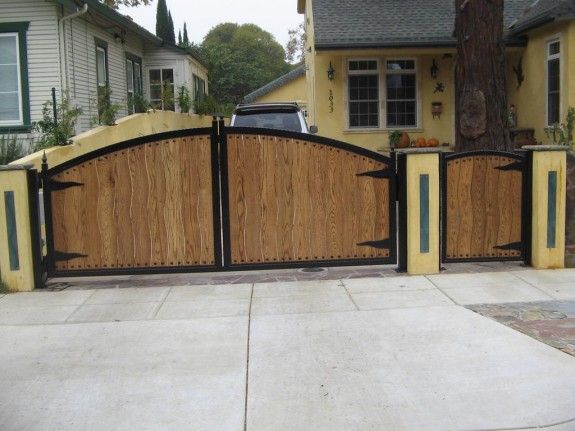 Accessories and Furniture. Iron Gates Home Entrance. Exterior Furniture Materials House Featuring Arched Top Swing Black Bronze Iron Main Entry Gate Inserted Wood Panels And Small Swing Secondary Entrance