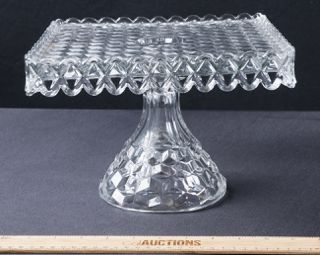 FOSTORIA GLASS COMPANY SQUARE PEDESTAL CAKE DISH. THIS 10 X 8 CLEAR GLASS PLATE IS IN THE AMERICAN CUBE PATTERN.