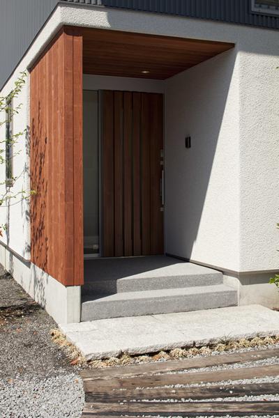 玄関前に半間引き込んだポーチは庇としての役割も 格子が和の雰囲気に