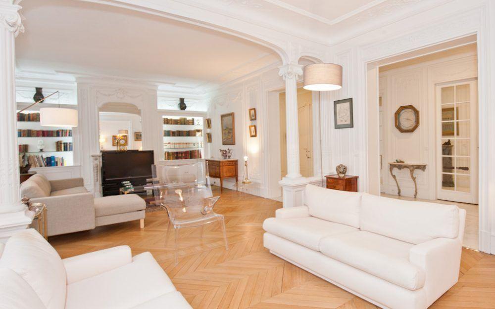 Salon d\'un appartement Haussmannien. Deux fauteuils blancs se font ...
