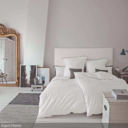 Holzdielen in Weiß, weiße Wände und helle Möbel lassen das Schlafzimmer erstrahlen. Ein Spiegel öffnet den Raum und gibt ihm zusätzlich Weite. In Szene gesetzte…