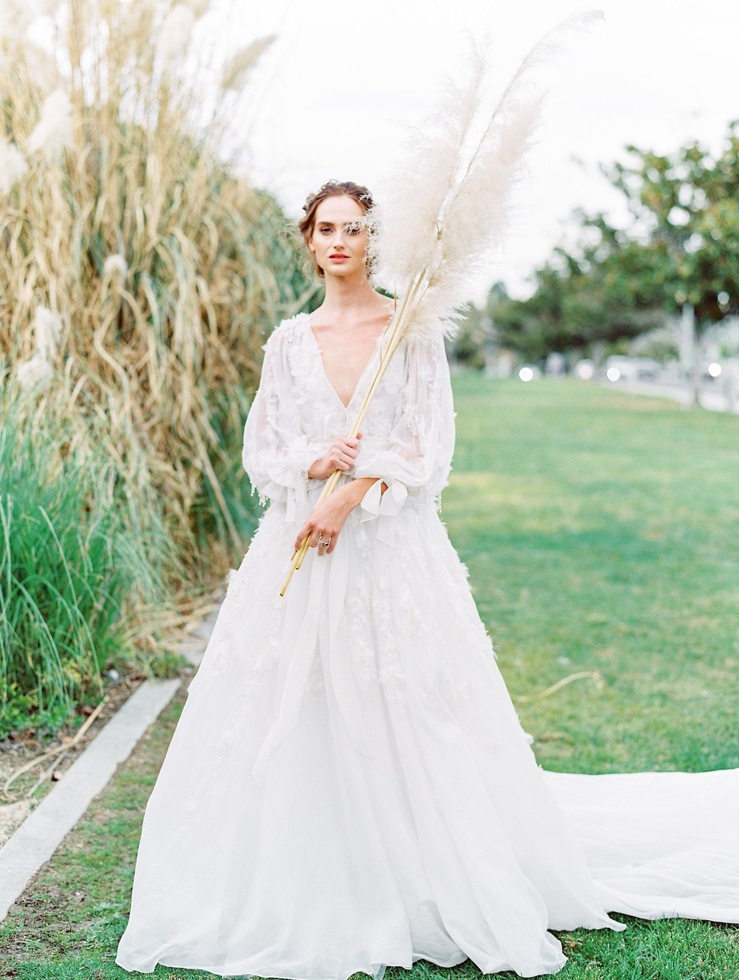 8540cfb7 Bride holding pampas grass wearing Long sleeve floral and feather Marchesa  gown from 2018 with tied