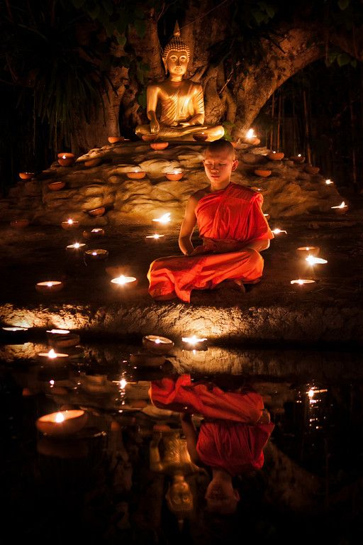 A young monk meditating during Visakha Bucha in Chiang Mai, Thailand. | Photo via Canvas of Light Photography