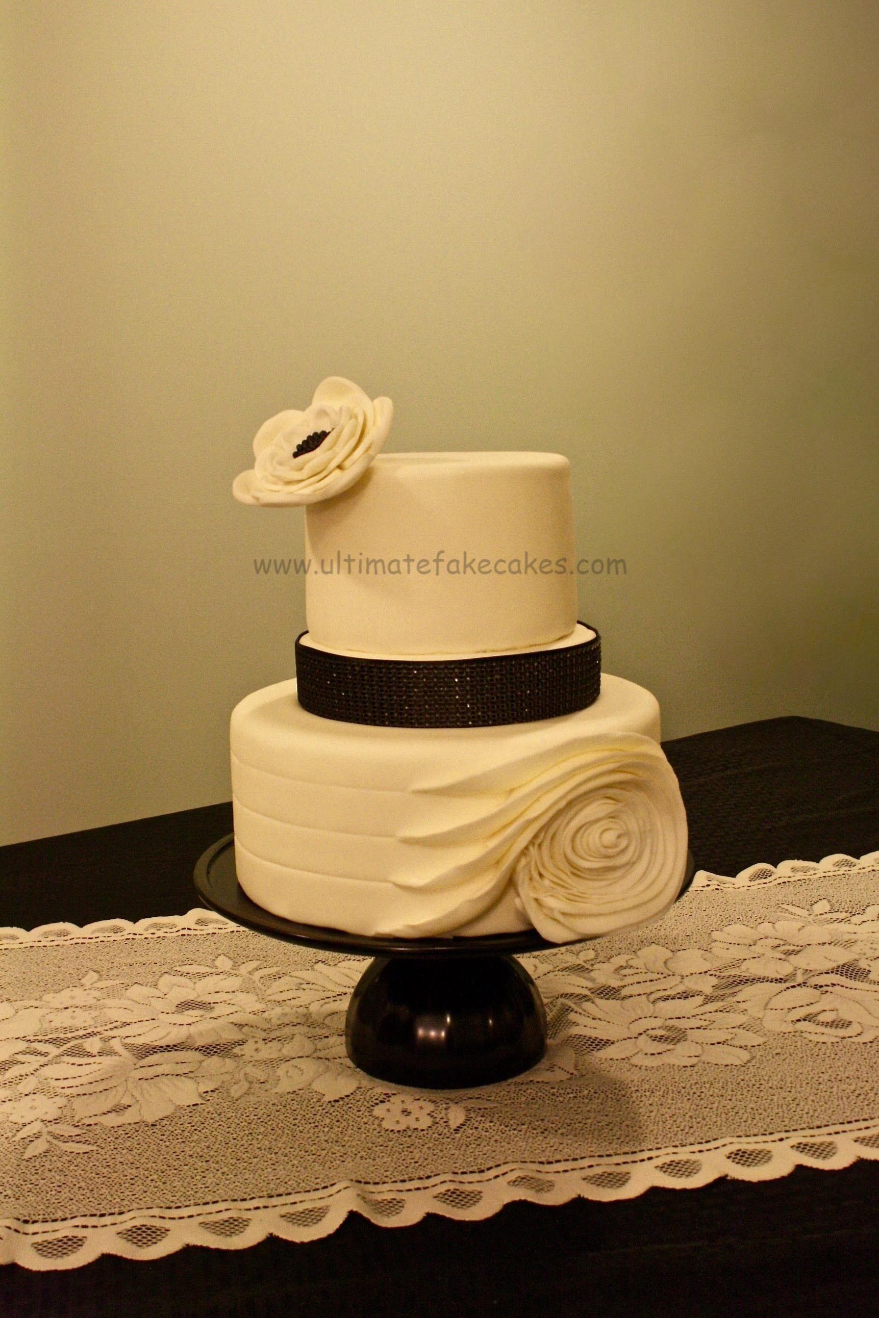 White ribbon rose cake with black rhinestone banding ...