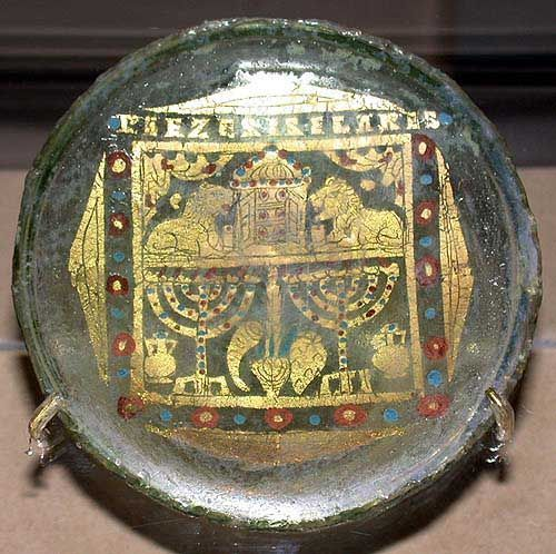 "4th C. Glass roundel  decorated in gold with a Torah Ark, two lions, two menorahs, and other Jewish symbols reads: ""Pie zeses, Elares"". In Greek, a toast : Drink so you may live.  It seems Romans of varied religions used the same workshops to make these and are presumed to have shared some secular rituals. Israel Museum, Jerusalem.:"