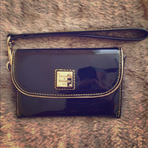 Dooney & Bourke Patent Wristlet Shiny black patent wristlet with red interior. Very good condition! One large slot and two smaller card slots. Snaps to open/close. Dooney & Bourke Bags Clutches & Wristlets