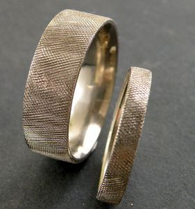 Knurled finish - that's Florentine in jeweler-speak.  Comfort fit, easy to wear, no fuss finish.  Choose your width and finger size.