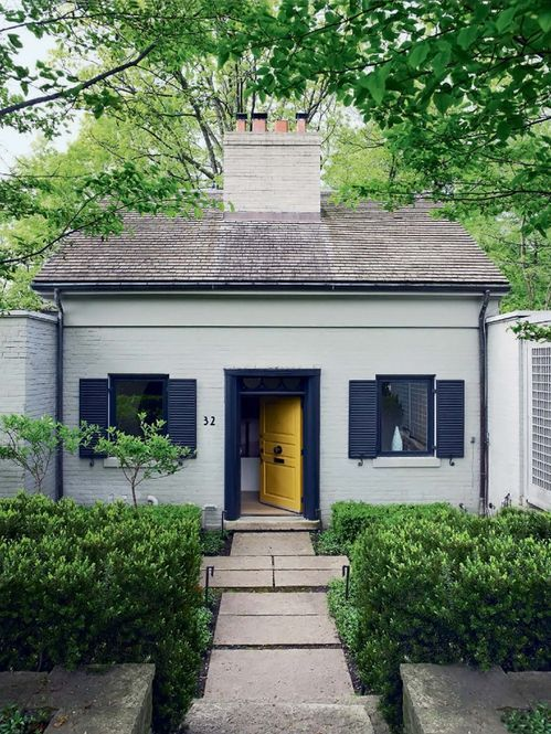 Navy trim and a yellow door make this exterior both stately and ...