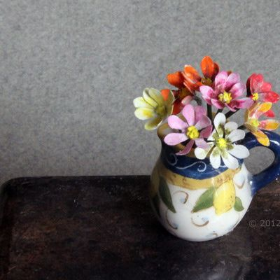Bouquet of various colored single dahlias made from punched paper petals in dollhouse scale.
