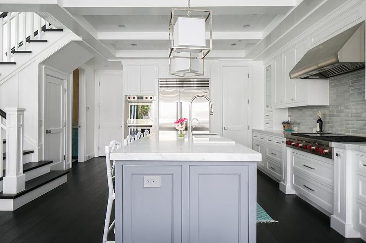 Exquisitely designed white kitchen features a four white bamboo counter stools placed on dark walnut stained wood floors in front of a gray island topped with a white marble countertop fitted with a sink and an oversize polished nickel gooseneck faucet illuminated by Caged Medium Lanterns.