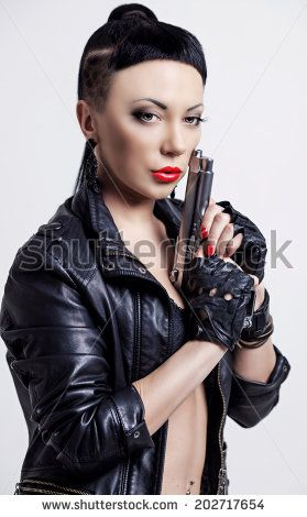 woman with modern unusual haircut with shaved sides and a fringe, holding a gun, against grey studio background - stock photo