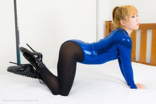 Mina is wearing a blue shiny bodysuit over black pantyhose and patent  ballet boots. She is hooded and gagged tightly in our Open Mouth Hood, ...