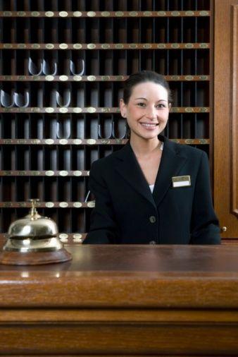Hotel Clerk Standing Behind Desk At Hotel Reception Hotel Services Hotel Reception Hotel Staff