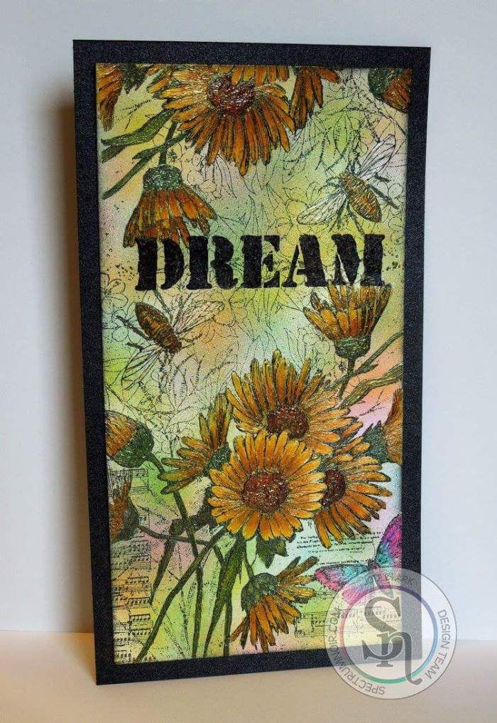 Designed by Jodi Clark for Spectrum Noir. Spectrum Noir markers Daisy – GB9, GB7, GB4.  Leaves – DG4, DG3, DG2. Butterfly – IB3, IB1, BP4, BP1. Background – LG5, BP2, CT3, PL3, IB2. Perfect Pearls Mists – Sunflower Sparkle, Forever Green, Mint, Kiwi, Sour Apple. Art Anthology Dimensional Paints – Dazzle, Kenyan Copper, Leaf, Vegas Gold. Art Anthology Sterling Fairy Dust shimmering spray. Stamp-Technique Junkies Vintage Daisy Collage. DREAM stenciled using Lava Stone Effects and Soliloquy…