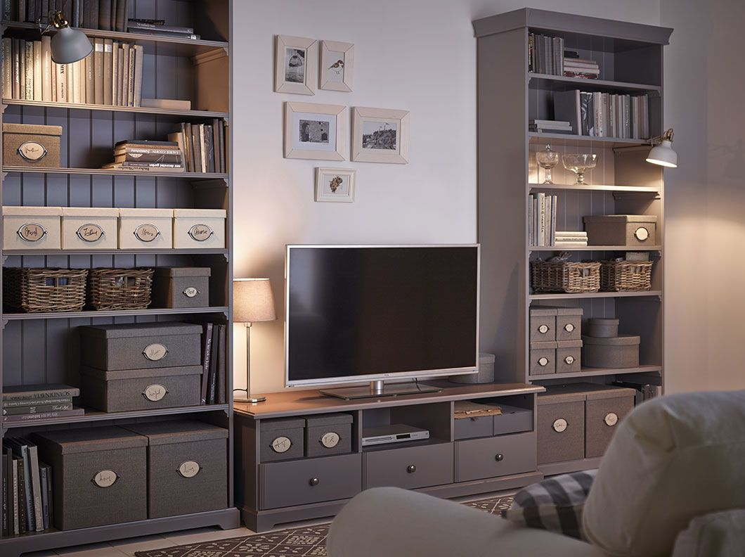 A Living Room With A White Tv Bench With Drawers And Two Grey