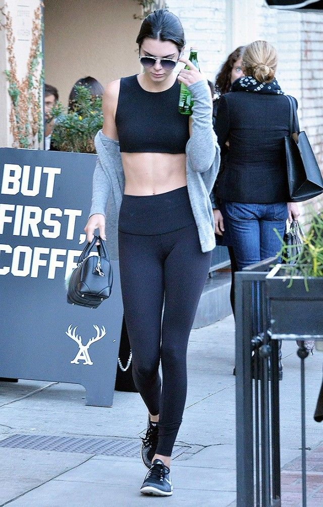 d71b0c06d2 Kendall Jenner wears a black sports bra, leggings, gray sweater, Nike  sneakers, Dior sunglasses, and a mini Givenchy duffle bag