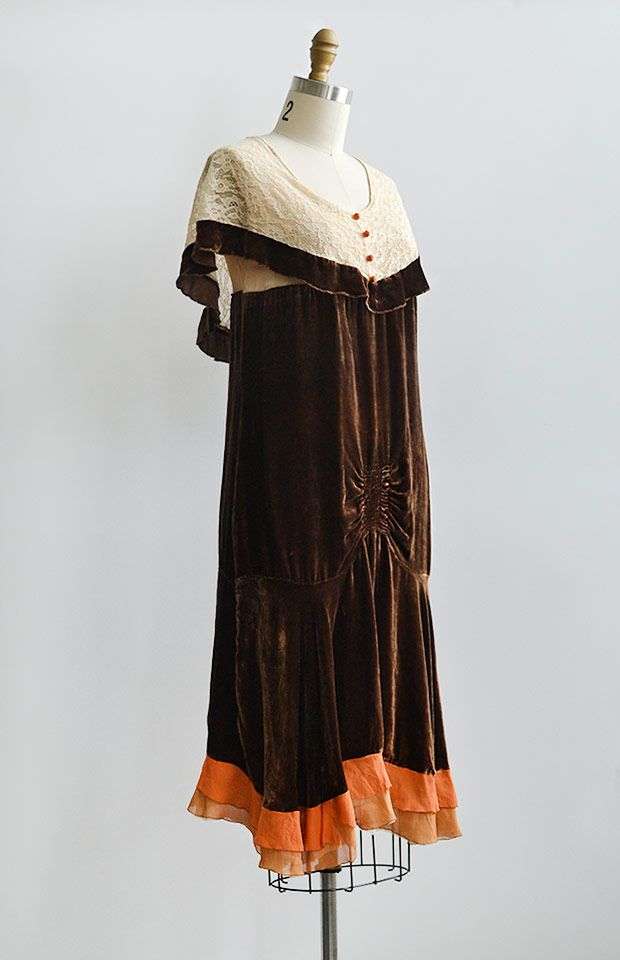 late 1920s brown silk velvet flapper dress. This vintage 20s dress features lace cape style sleeves with decorative buttons,  ruche detail on drop waist, and cream and orange silk chiffon ruffle on hem.