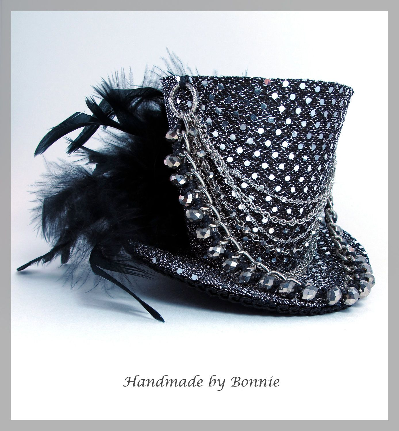 I love the decoration on this mini top hat - the chains and all of that draped from the back to the front and back again.