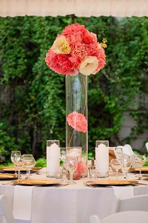 Decorations tips balance bright pink peonies atop a tall