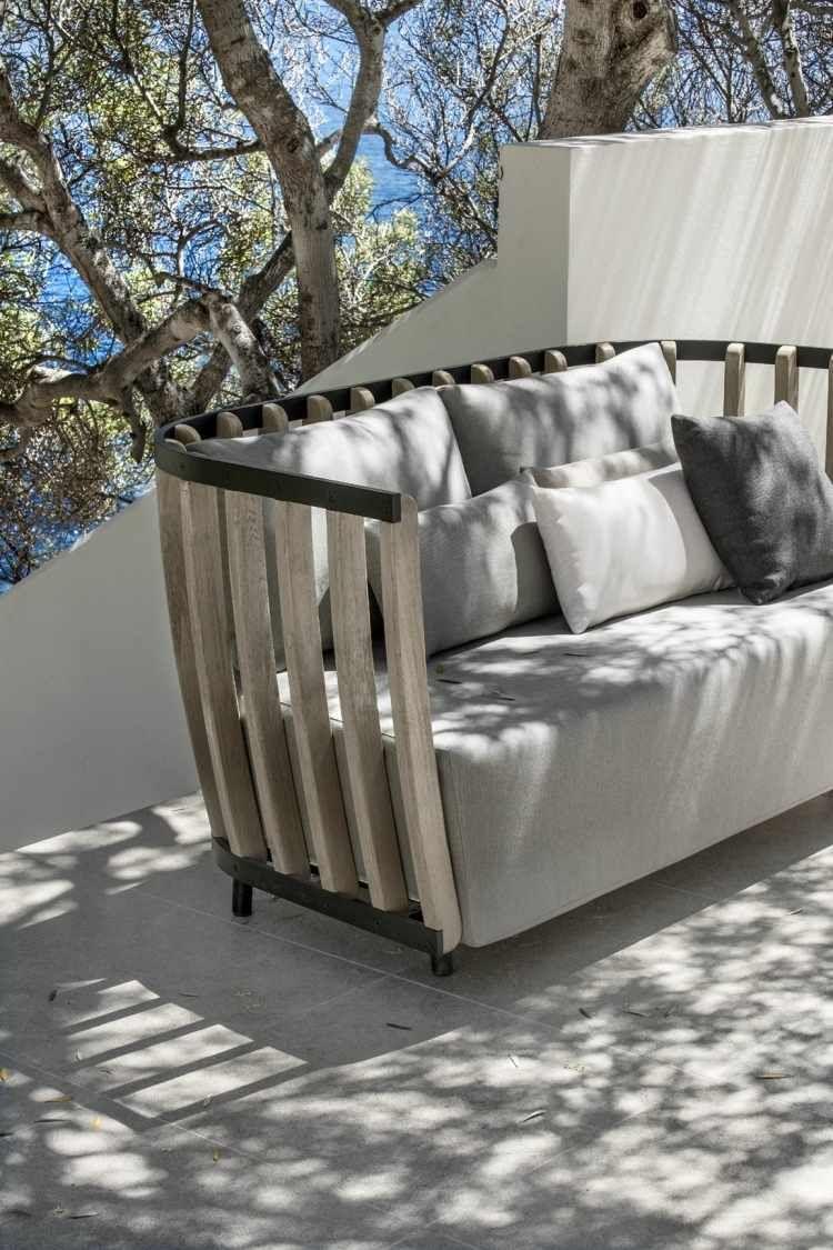 canape de jardin en teck decore de coussins en gris et blanc et dote accoudoirs