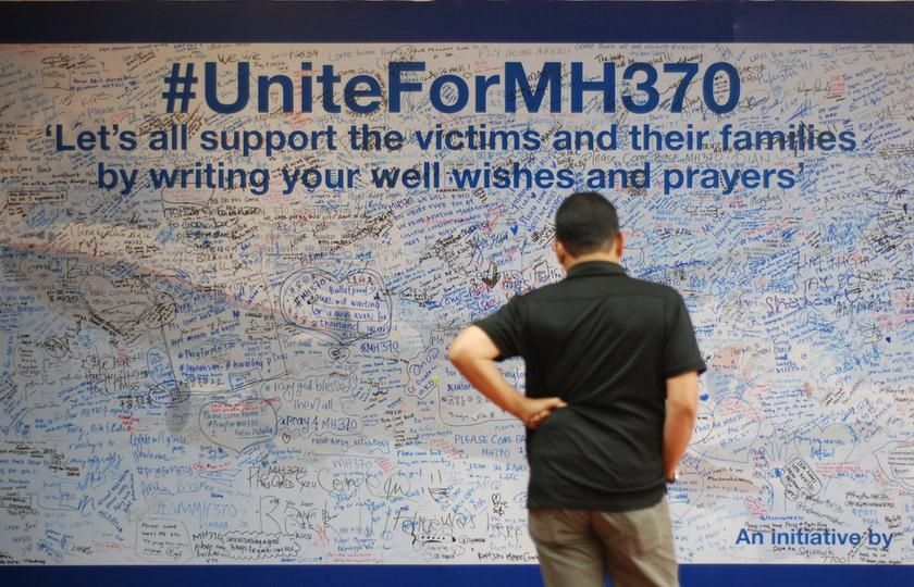 A man looks at messages of support left for family members and passengers onboard the missing Malaysia Airlines Flight MH370 at The Curve, Petaling Jaya March 18, 2014. — Picture by Yusof Mat Isa