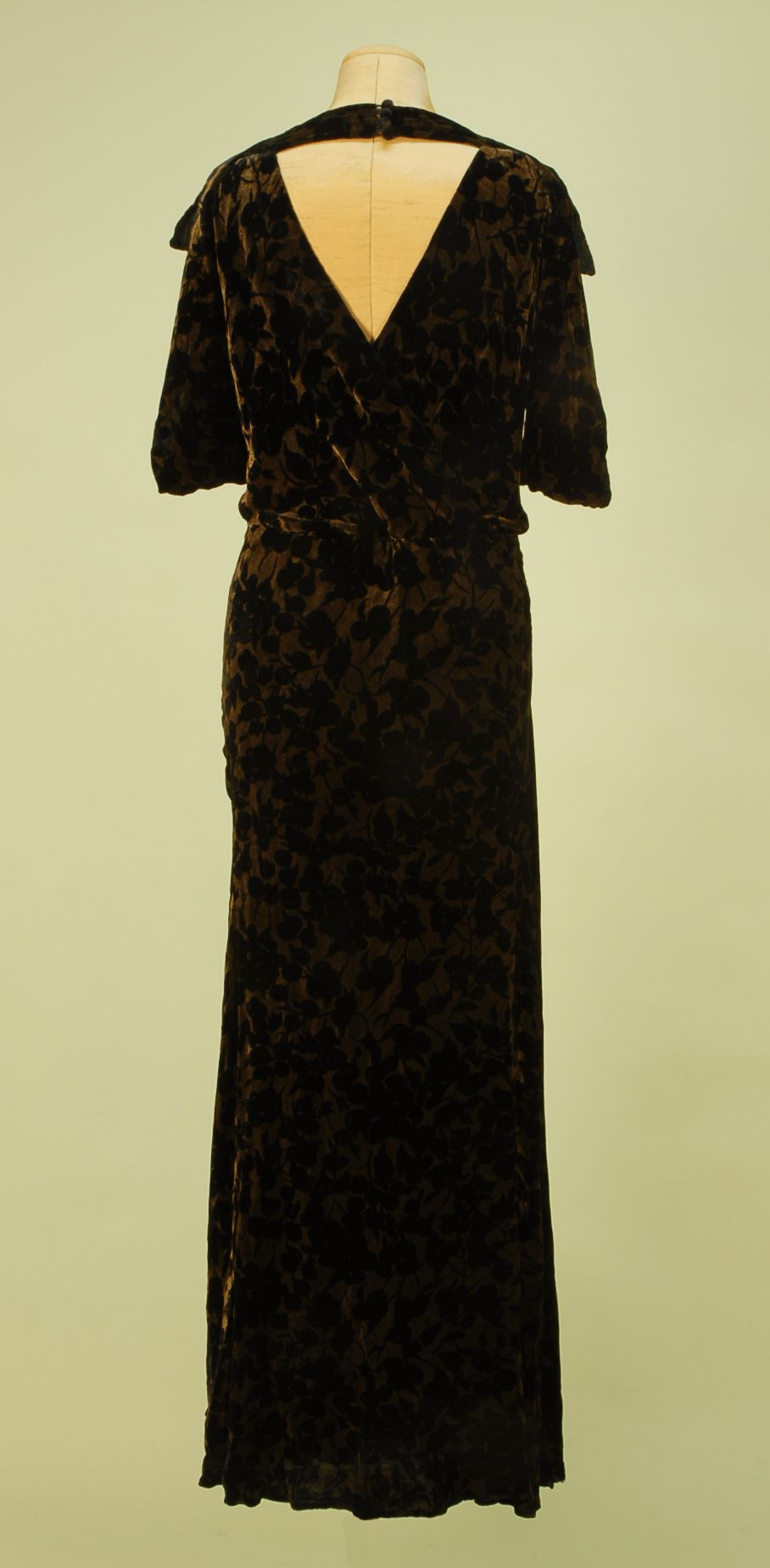 Back View VOIDED VELVET and GOLD BIAS CUT EVENING GOWN, c. 1930. Black velvet in an overall pattern of cherries on a metallic gold ground with draped cutout V-back with four self button and loop closures at top, slight cowl front, pointed cap sleeve and unusual looped arm treatment.