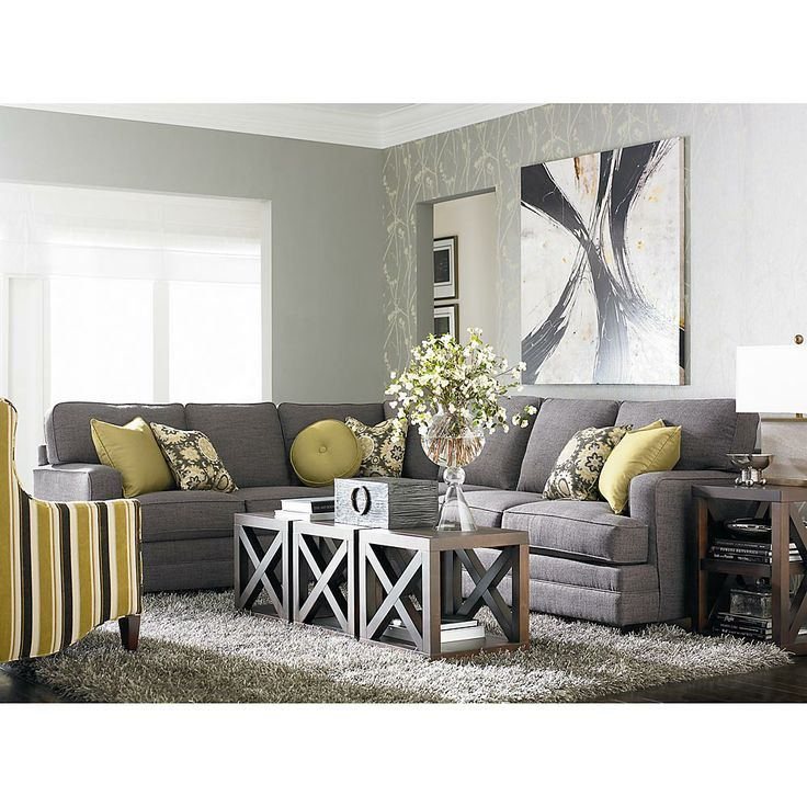 This grey sofa shows off the yellow and printed pillows ...
