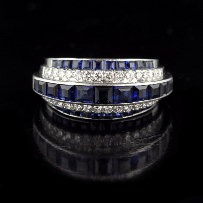 Period  c1950   Origin  American   Gemstones  Diamonds est 0.70cts  Calibre-cut sapphires est 2.0cts   Setting  Platinum   Dimensions  UK size M 1/2 / US size 7  2.4cm x 1.1cm