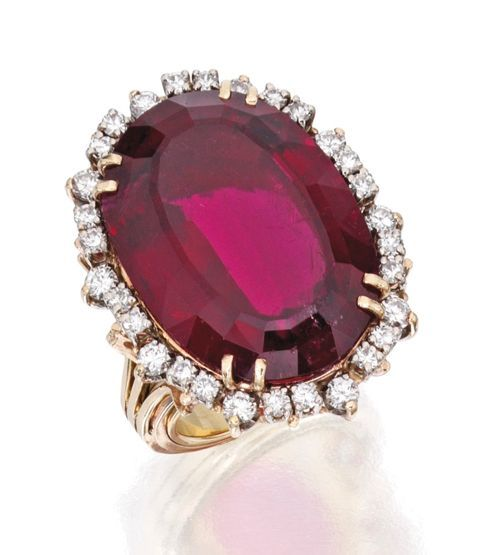 GOLD, RUBELLITE AND DIAMOND RING The oval-shaped rubellite weighing approximately 40.00 carats, framed by round diamonds weighing approximately 1.40 carats