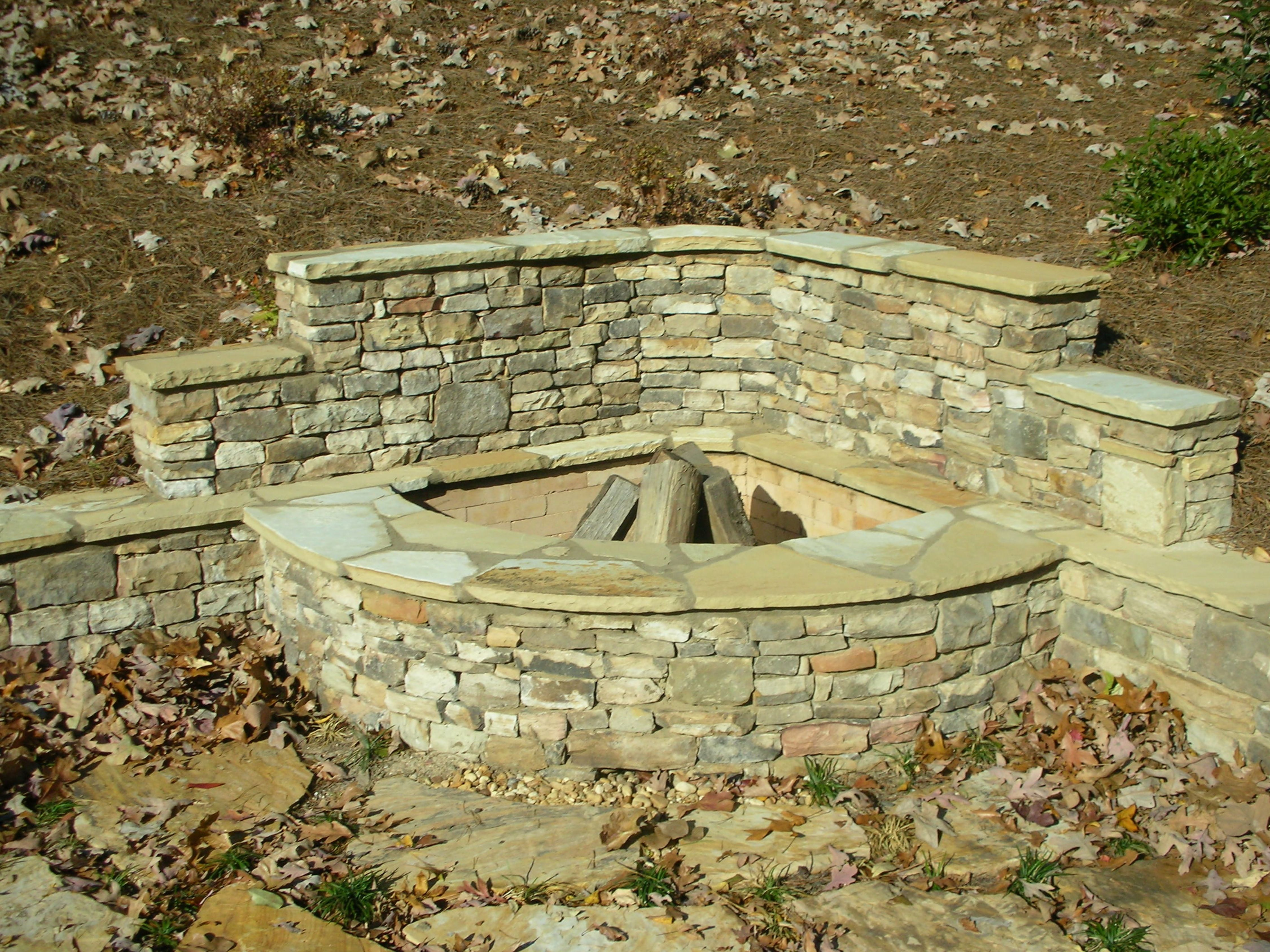 Stacked Stone Corner Firepit with Retaining Wall | Fireplaces and ...
