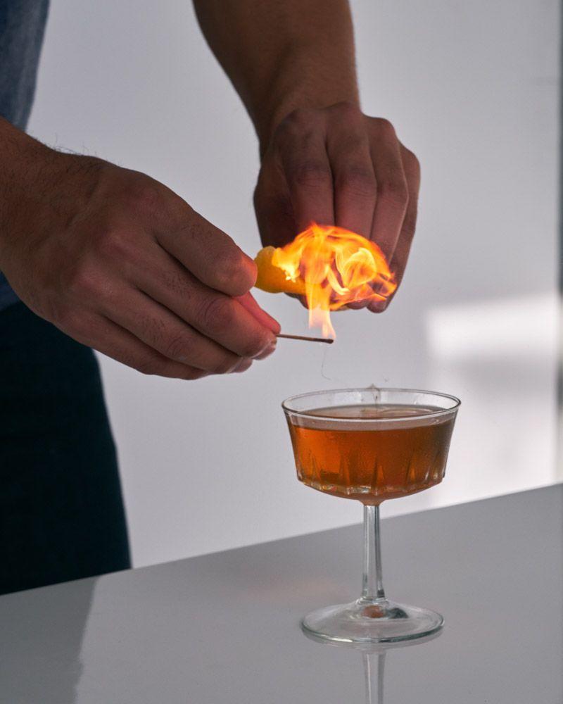 Flaming an orange peel for a chile manhattan recipe