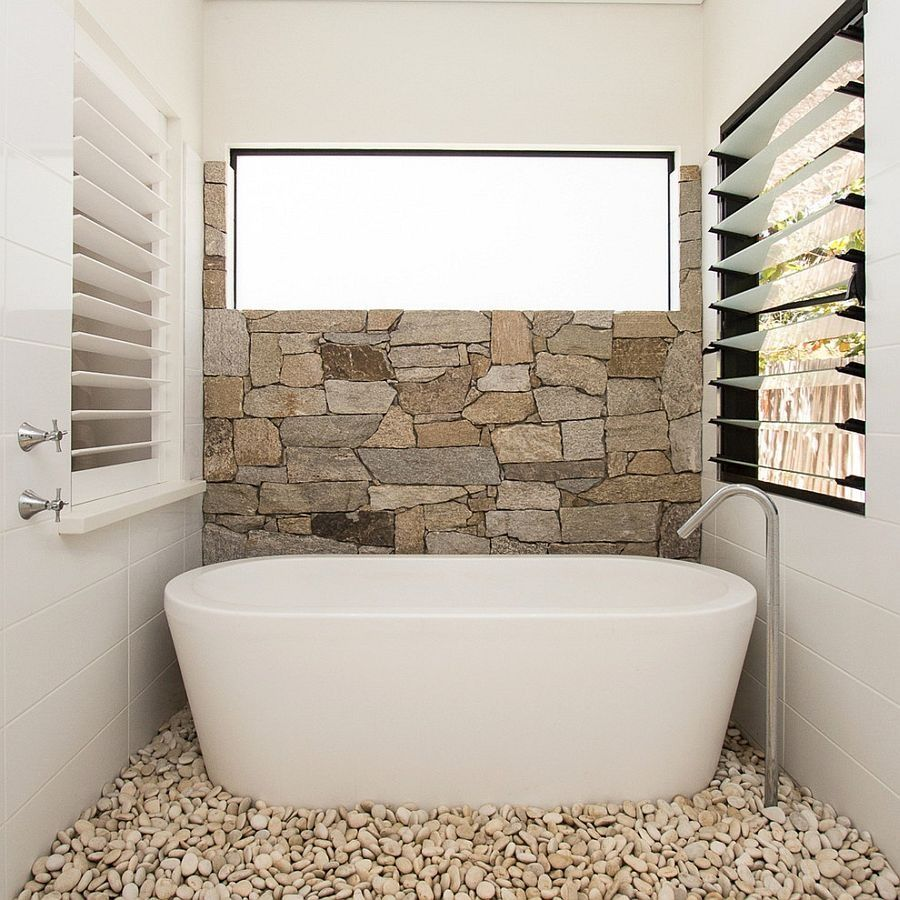 Small Bathroom With Natural Stone Wall Containing Gravel Flooring With Freestanding Tub Also