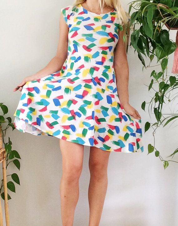 •circa 1980s one of a kind mini dress •super comfortable light cotton and fun multi-color novelty print •sides of dress are slightly longer info: material: cotton color: white with red, green, blue + yellow condition: excellent vintage condition (no major flaws to note)  measurements {taken lying flat} bust: 16 (pit to pit) dress length: 36 dress waist: 15 est. size: ladies modern small/medium marked size: none tag: none  model is 58 and wears a typical medium size. c cup. accessories ar...
