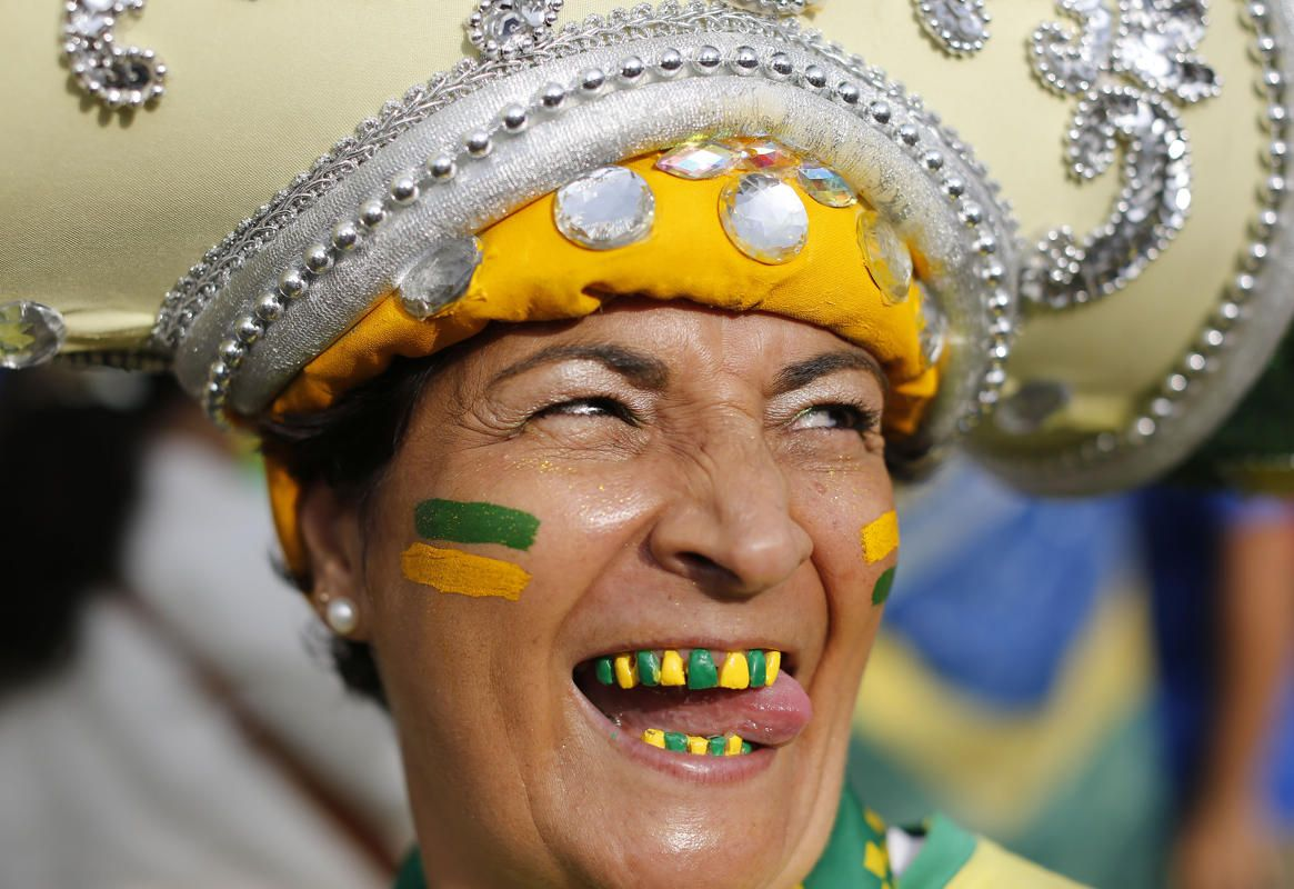 A Brazil soccer fan with her teeth decorated in the colors of her soccer team poses for a photo before watching the World Cup semifinal match between Brazil and Germany on a live telecast inside the FIFA Fan Fest area on Copacabana beach in Rio de Janeiro, Brazil, Tuesday, July 8, 2014.