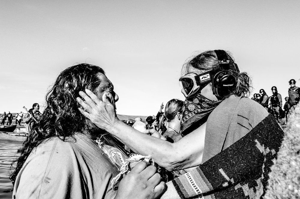 Riot Police Injure Over 100 People Defending Standing Rock Burial Grounds - On Wednesday, November 2, law enforcement desecrated the burial grounds of  Alma Parkin and Matilda Galpin, the indigenous women who once owned the  Cannonball Ranch. As water protectors held a water ceremony, snipers shot  at them from armored vehicles parked around the tree marking the graves.