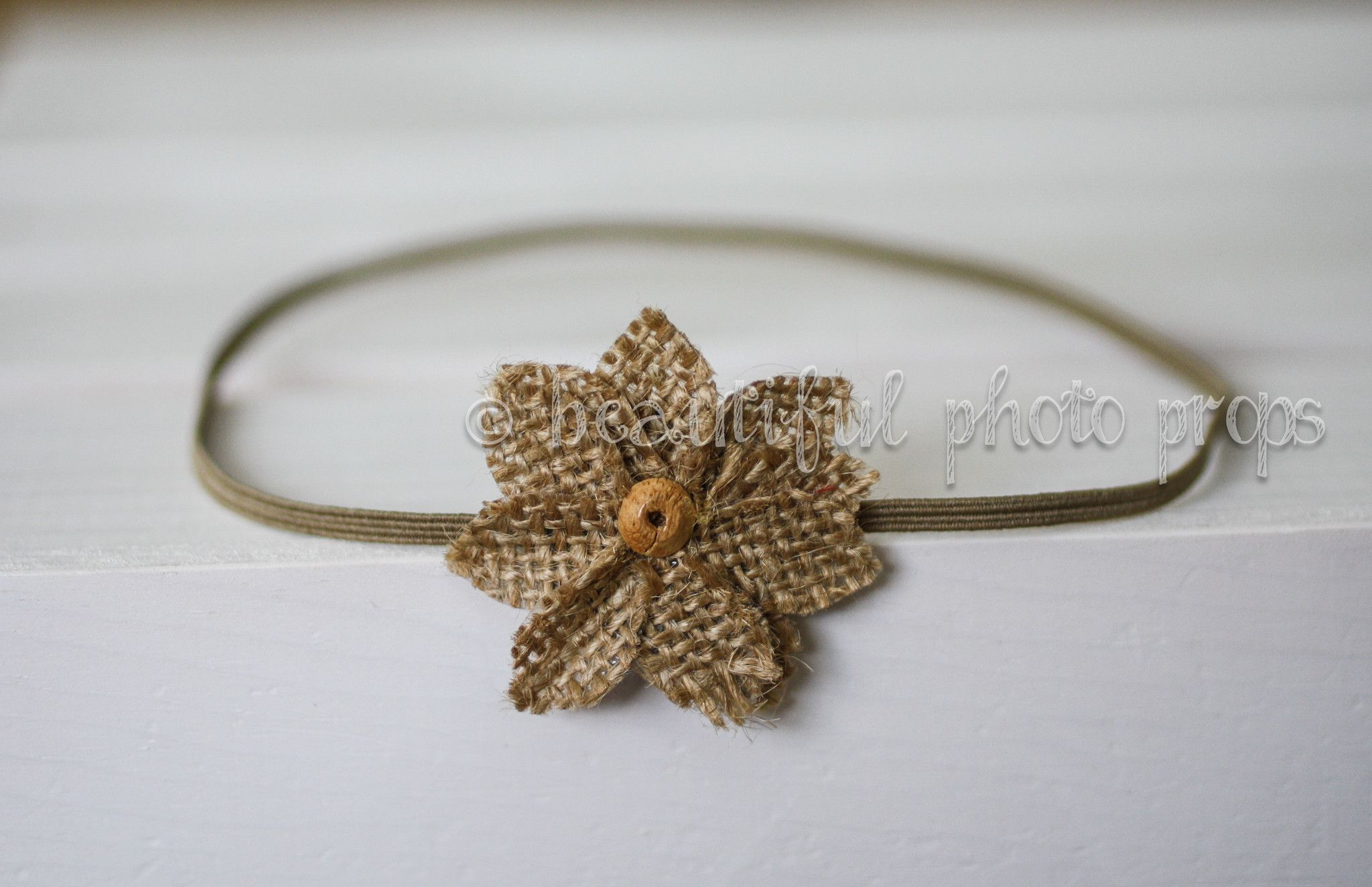 Beautiful beige burlap flower with button center on a skinny elastic band.