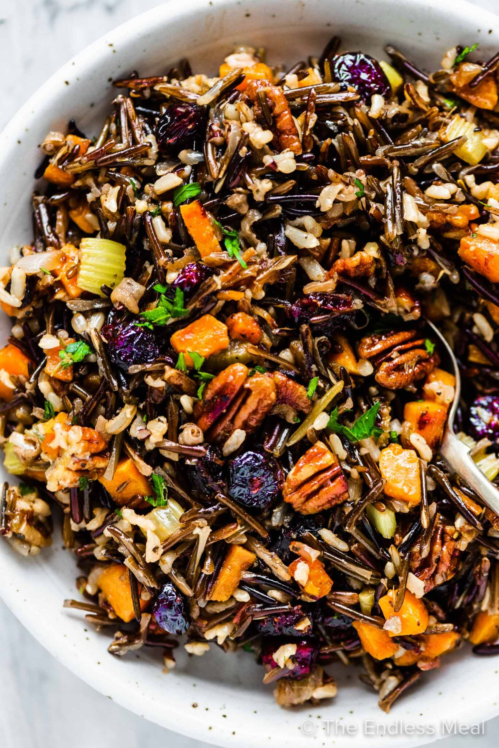 PIN TO SAVE! Our favorite wild rice stuffing is made with a wild rice blend cooked in a flavorful broth then mixed with cranberries, pecans, and sweet potatoes. #theendlessmeal #wildricestuffing #wildricepilaf #ricepilaf #wildrice #ricestuffing #stuffing #dressing #thanksgiving #thanksgivingrecipe #christmas #christmasdinner
