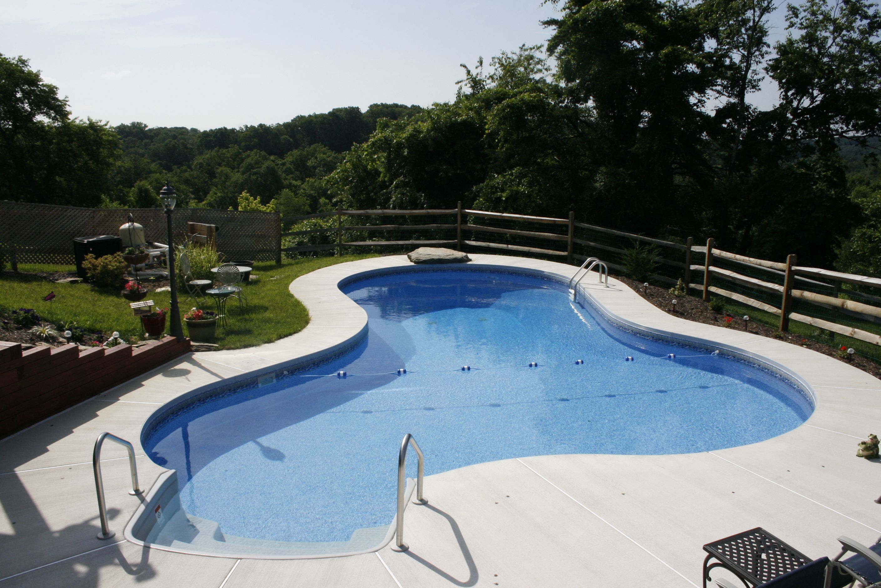 Lagoon style pool featuring brushed concrete deck