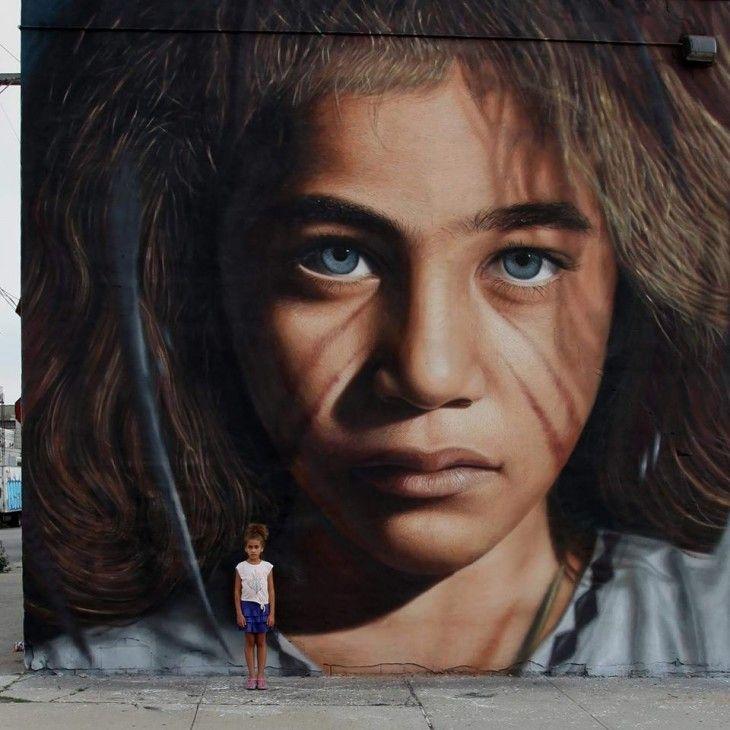 Niña parada frente a una pared que tiene dibujado un rostro de una niña