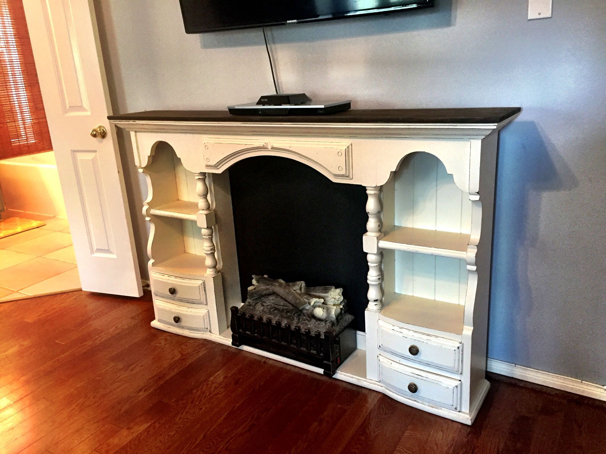 Cute repurposed 80's style dresser or buffet top... Makes a sweet country faux fireplace for a bedroom. Think maybe for guest rooms. Cozy.