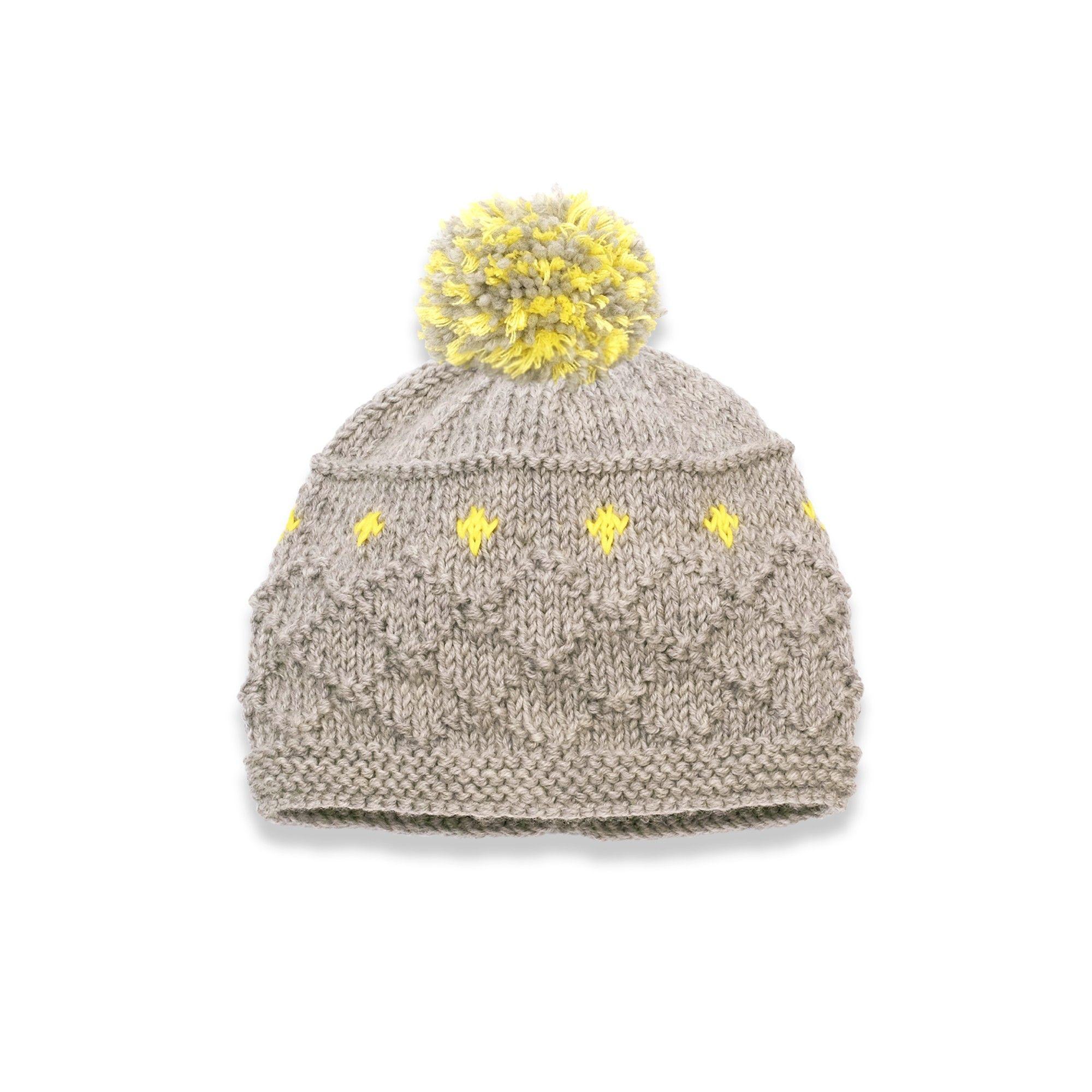 Bonnet bébé gris clair orné d étoiles jaunes avec un pompon gris et jaune. 8677db8fc5b