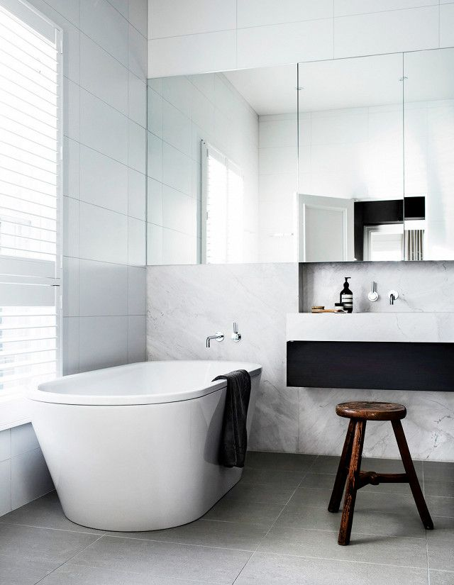 Minimalist Bathroom With Marble And Tile Walls A Free Standing Tub Wooden Foot Stool