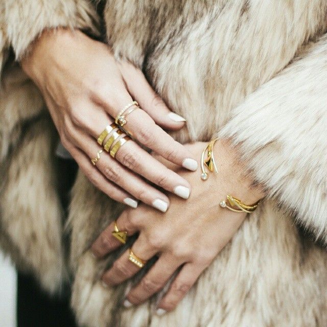Faux fur and gold stacked rings paired with white nails. We love this look.