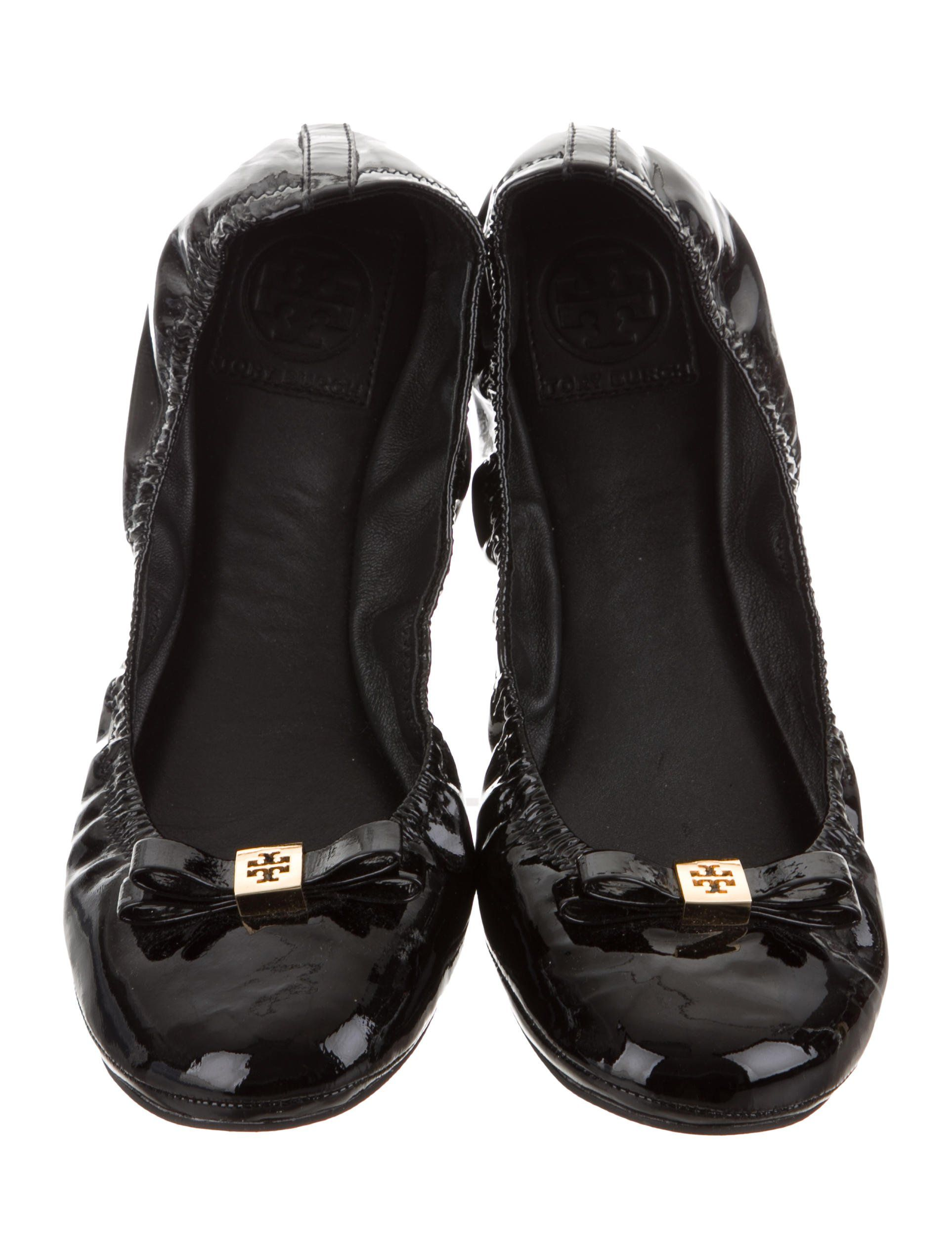 546f7ab7e Black patent leather Tory Burch ballet flats with bow accent at vamps,  gold-tone logo hardware, elasticized toplines and rubber soles.