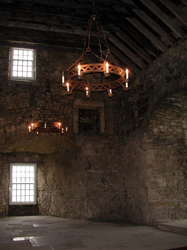 This stone chamber on the interior of a medieval castle has a very high ceiling and surprisingly large windows.