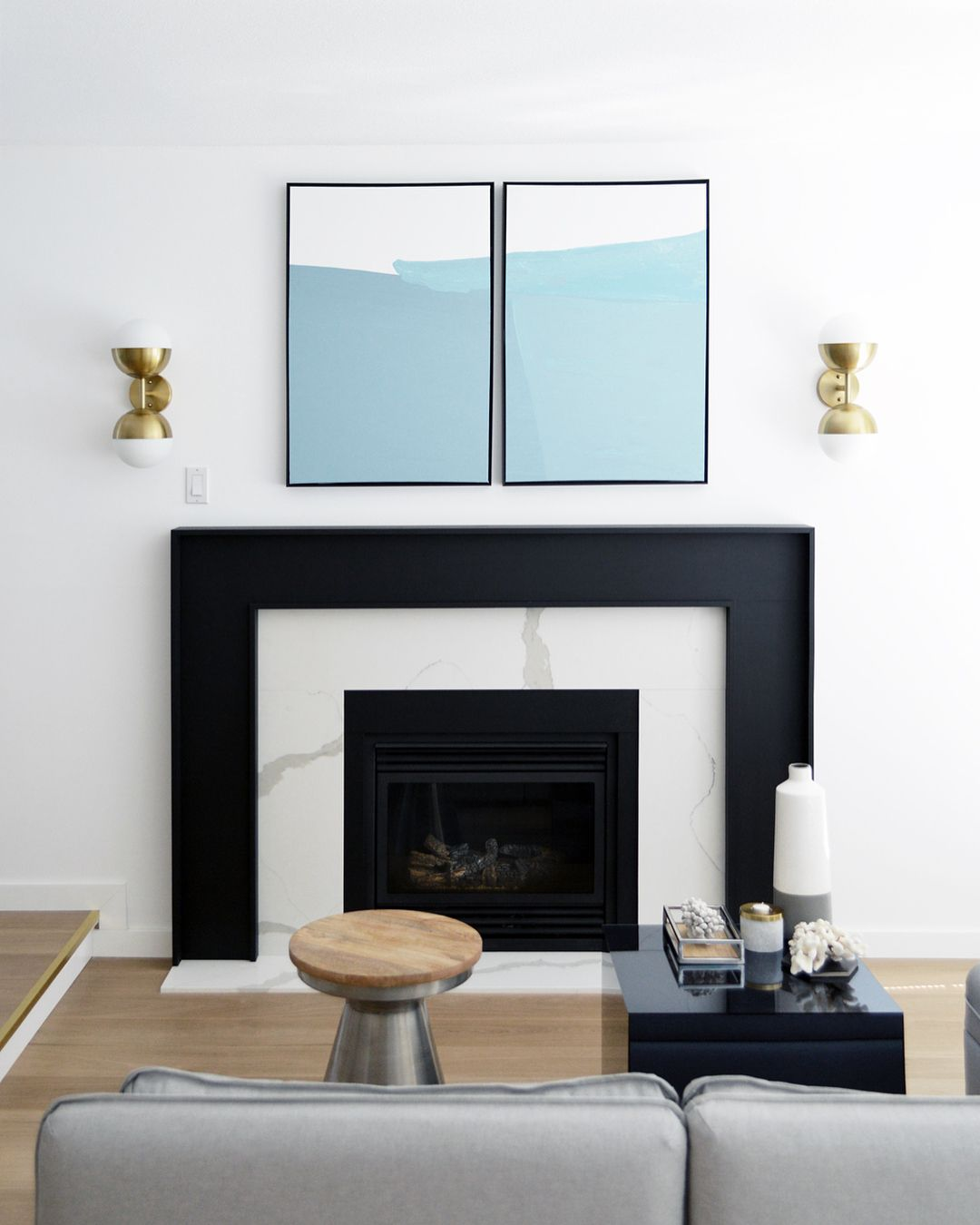 Modern Black And Marble Fireplace Flanked By Brass Sconces With Minimal Turquoise Artwork Modern Fireplace Mantles Boho Living Room Decor Sconces Fireplace