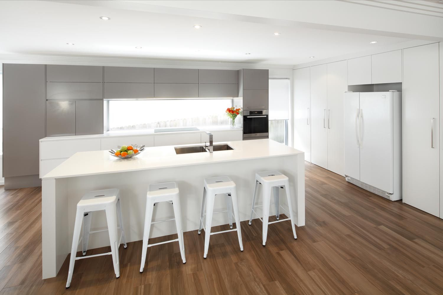 This Sleek Modern Kitchen Design Incorporates White Silver And Beautiful Timber Flooring