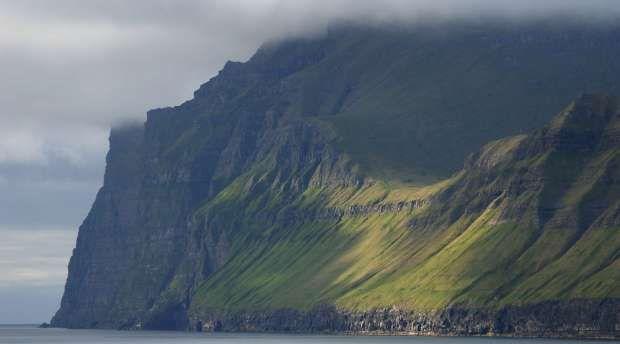 Kallur pynt og fuglefjeld med stejle klippeafsatser højt over havet på nordspidsen af Kalsoy øen , ...